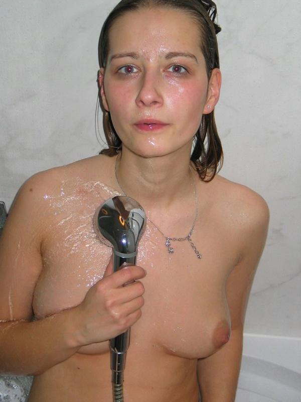 Молоденькая девушка из деревни снимает лифчик рядом с окном и принимает душ