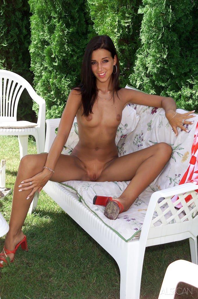 Обнаженная милаха спокойно дрочит розовую щелка на скамейке