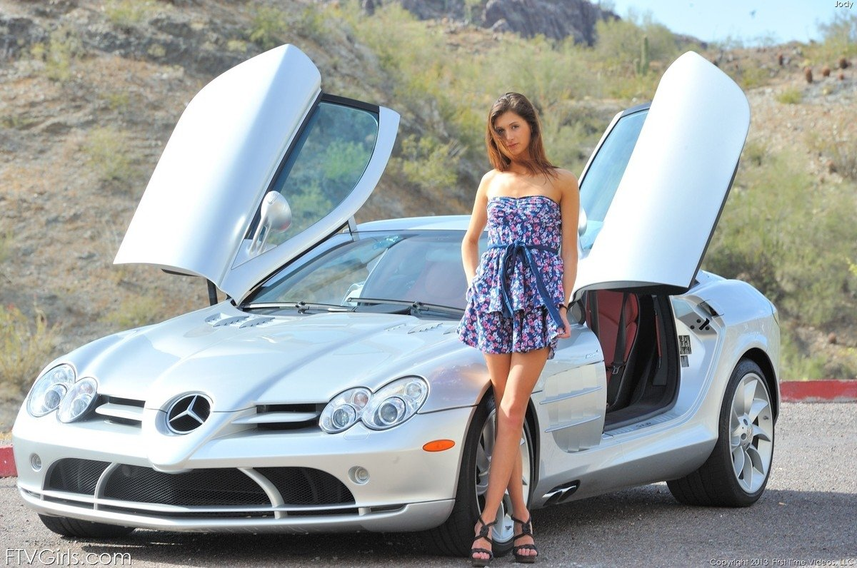Грациозная милашка в коротком платье показывает свое горячее туловище вблизи от спортивной машины